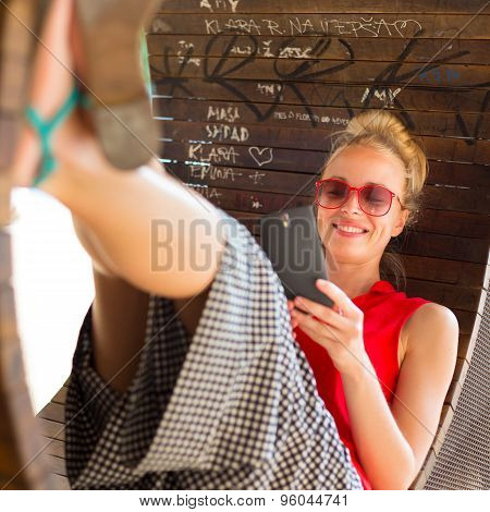 Young cheerful woman using smarthphone.