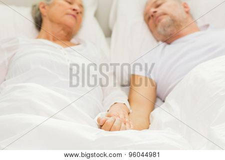 family, bedtime, resting, age and people concept - close up of senior couple lying in bad and sleeping at home