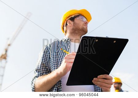 business, building, paperwork and people concept - builder in hardhat with clipboard and pencil outdoors