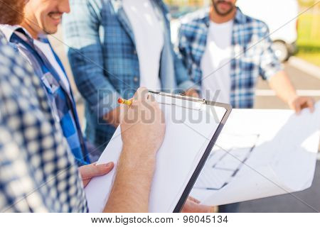 building, construction, development, teamwork and people concept - close up of builders with clipboard and blueprint