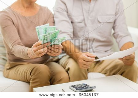 family, business, savings age and people concept - close up of senior couple with papers, money and calculator at home