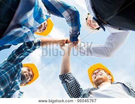 business, building, partnership, gesture and people concept - close up of smiling builders in hardhats making high five outdoors
