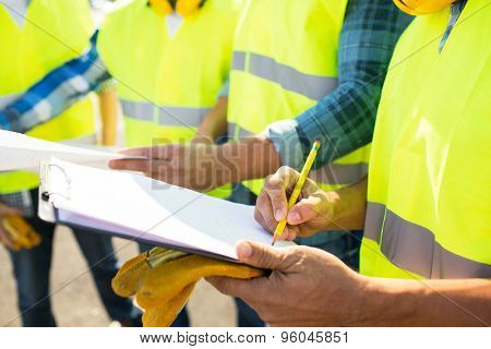 industry, building, paperwork and people concept - close up of builders in high visible vests writing to clipboard