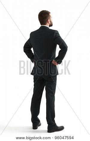 back view of businessman in formal wear looking up at something. isolated on white background