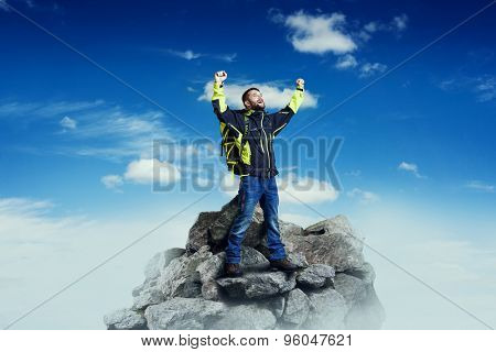 happy tourist raising his hands up and screaming on rock over blue sky