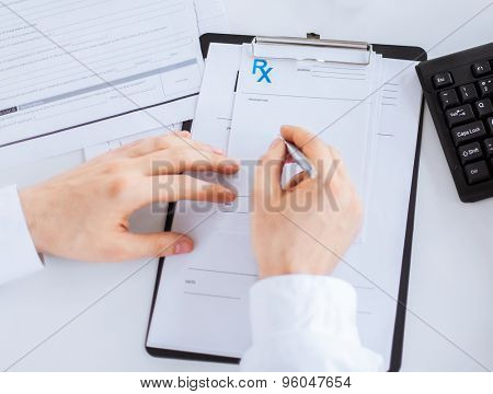 close up of male doctor writing prescription paper