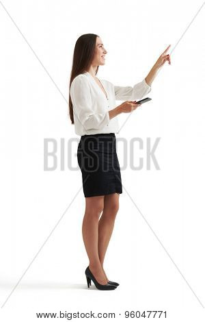 sideview portrait of businesswoman in formal wear holding smartphone and pointing at something. isolated on white background