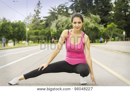 Hispanic brunette in yoga clothing stretching her right leg and looking at camera smiling