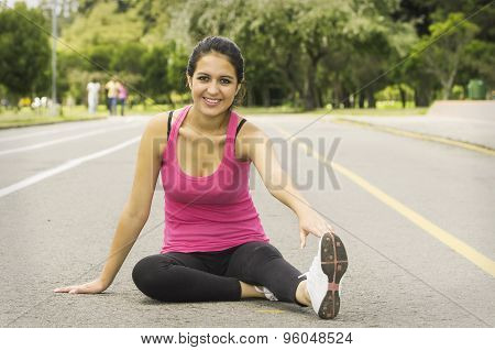 Hispanic brunette wearing training clothes sitting on hard surface in park environment doing stretch