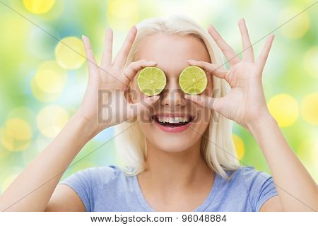healthy eating, organic food, fruit diet, comic and people concept - happy woman having fun and covering her eyes with lime slices over summer green holidays lights background