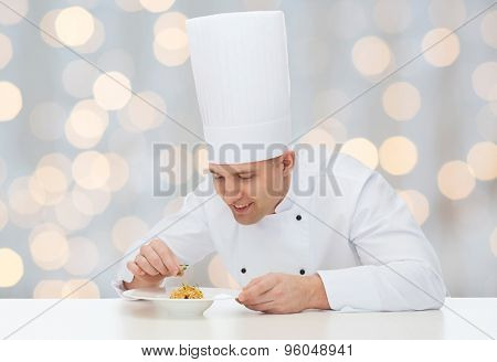cooking, profession, haute cuisine, food and people concept - happy male chef cook decorating dish over holidays lights background