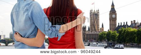 people, homosexuality, same-sex marriage, travel and gay love concept - close up of happy lesbian couple hugging over big ben and houses of parliament in london background