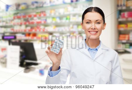 medicine, pharmacy, people, health care and pharmacology concept - happy young woman pharmacist with pills over drugstore background