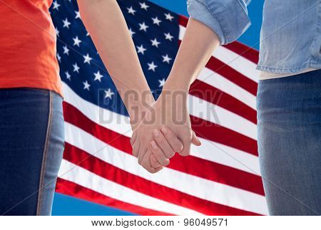 people, homosexuality, same-sex marriage, gay and love concept - close up of happy lesbian couple holding hands over american flag background