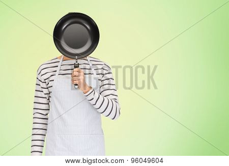people, cooking, culinary and identity concept - man or cook in apron hiding his face behind frying pan over green natural background