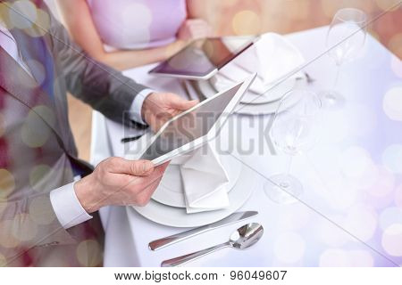 technology, people, food and holiday concept - close up of couple with menus on tablet pc computers at restaurant over holidays lights background