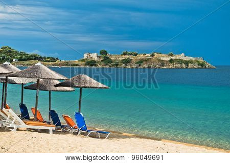 Beachscape with orange chairs, straw sunshades, old roman fortress in background