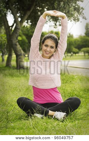 Hispanic brunette in yoga clothes sitting on grass with legs crossed and stretching both arms above