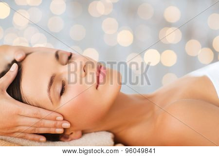 spa, beauty, people and body care concept - beautiful woman getting face treatment over holidays lights background