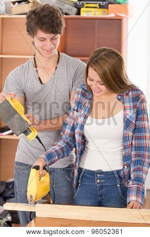 Couple renovating with tools as woman using jigsaw on wooden board and man standing beside her holdi