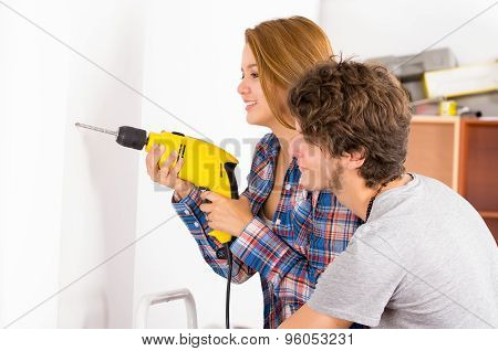 Couple renovating together as woman using power drill on wall with man standing next to her observin