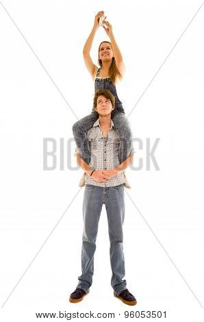 Woman sitting on mans shoulders while she assembles something high up and he looks upwards
