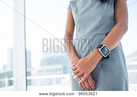 Businesswoman wearing a smartwatch with arms folded in the office