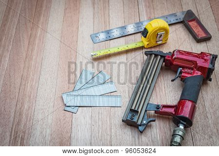 Close Up Air Nail Gun With Measurement Tools On Wood