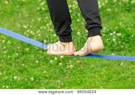 Closeup man feet walking on slackline and grassy background shot from side behind