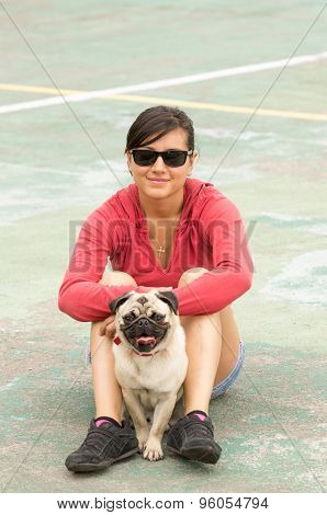 Hispanic beautiful woman with sunglasses and pug dog looking down sitting together in a tennis court
