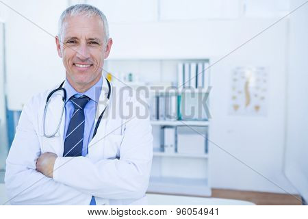 Happy male doctor looking at camera with arms crossed in medical office