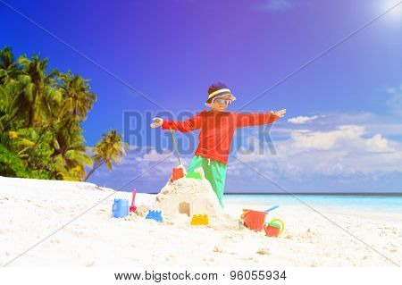 little boy building sandcastle on tropical beach