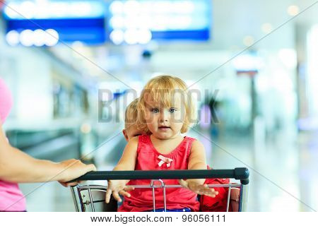 mother and kids on luggage cart in the airport