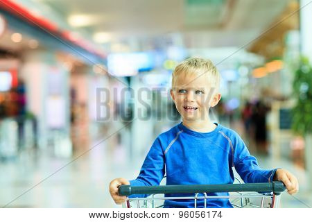 Happy cute boy at airport riding on luggage cart