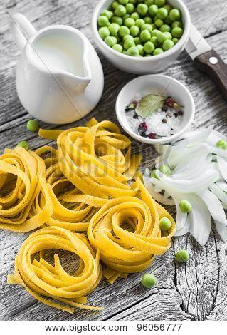 Raw Ingredients - Homemade Pasta, Green Peas, Onions, Cream, Light Wooden Background