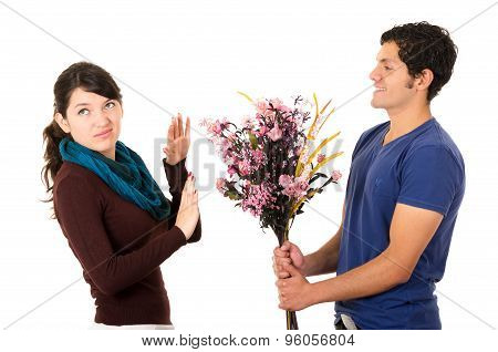 Man tries to give girlfriend flowers but she dimsisses him by holding up her hand and looking upset