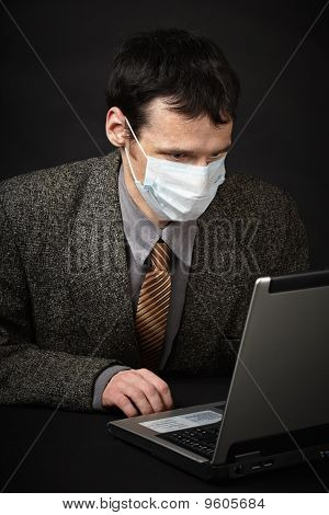 Man In Medical Mask Diagnoses Computer