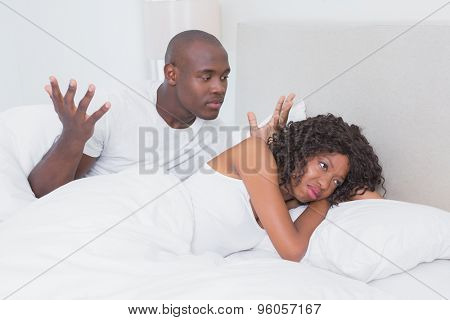 Dispute between a couple in bed together at home in bedroom