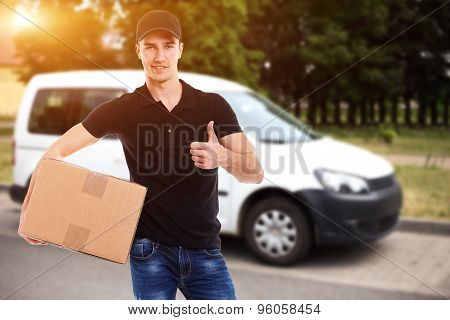 Smiling Delivery Man With A Paper Box In Sunlight