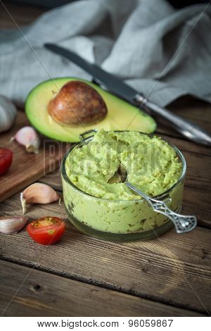 Guacamole On Wooden Table Surrounded By Its Ingredients..