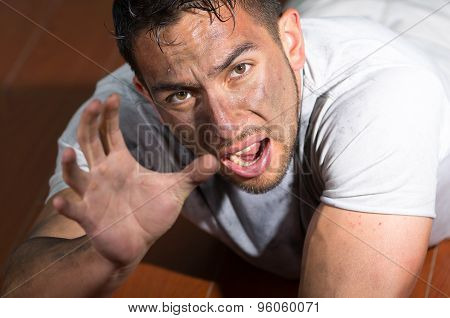 Hispanic man with dirty face and shirt lying on floor looking desperately to camera reaching right h