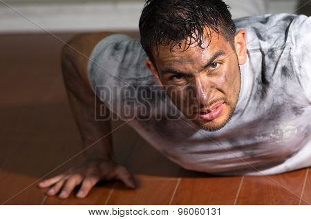 Hispanic man with dirty face and shirt lying on wooden floor pushing himself up using arms looking t