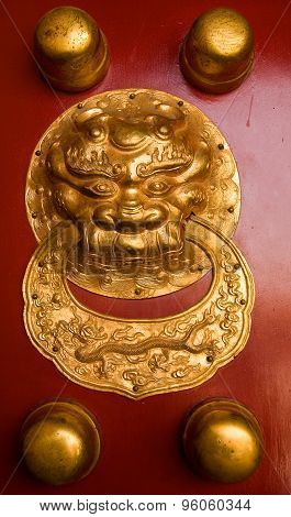 Golden dragon face ornament on a red door