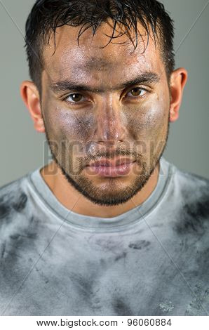 Hispanic man with dirty face and shirt looking to camera serious facial expression