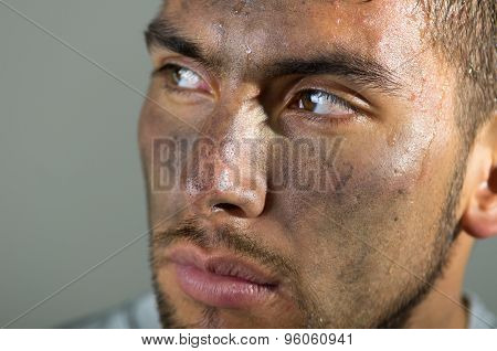 Closeup of hispanic man dirty face looking focused to side direction