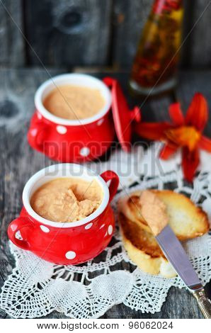 Pate in the red ramekin on the vintage napkin with toast