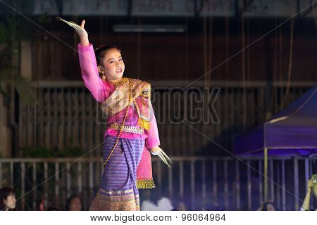 CHIANG MAI, THAILAND, JANUARY 04, 2015 : A woman is performing a Thai traditional dance at an outdoor stage during the Saturday night street market in Chiang Mai, Thailand