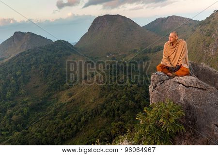 CHIANG DAO, THAILAND, JANUARY 05, 2015 : A Buddhist monk master is meditating at the top of the Chiang Dao mount at dusk for the new year in Thailand.