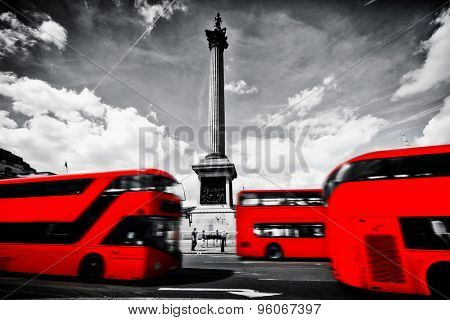 Red buses in motion on Trafalgar Square in London, UK. Nelson's column, black and white cloudy sky.