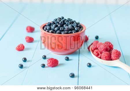 fresh blueberries in a bowl and berries on light wooden rustic background, closeup, horizontal, clos